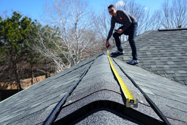 Inspekcja przed sprzedażą domu. obrazek prezentujący osobę wykonującą inspekcję na dachu domu. w tym wypadku korzysta on z miarki, stoi na szczycie dachu